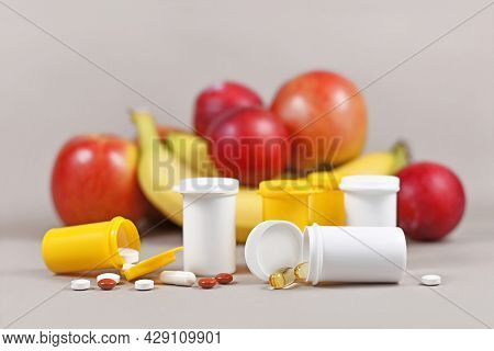 Food Nutrition Supplement Capsules And Pills With With Plastic Bottles In Front Of Fruits