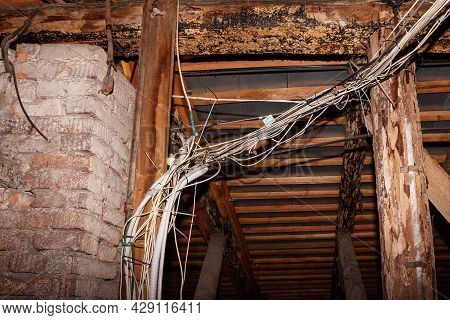 Messy Bundle Of Wires And Cables In The Attic Of A House With Wooden Rafters