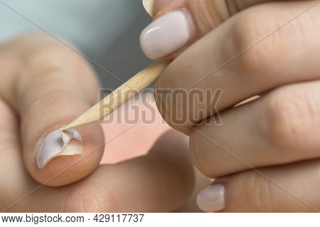 Remove The Gel Polish With A Wooden Stick. Woman Is Removing Gel Polish Shellac From Nails Using Pus