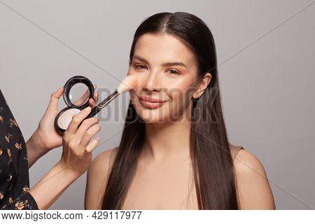 Makeup Concept. Close Up Make-up Artist Hands Applying Powder And Highlighter On Client Skin
