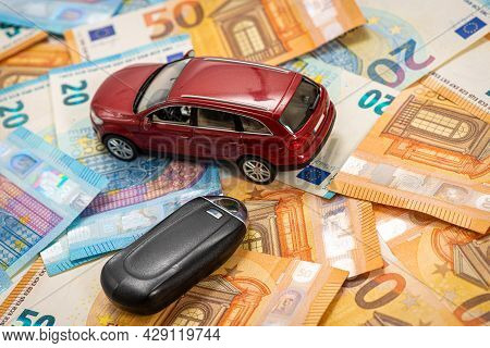 Key And Red Toy Car On Pile Of Euro Bills, Buy Or Sell A Car, Rent A Car Or Insurance Concept