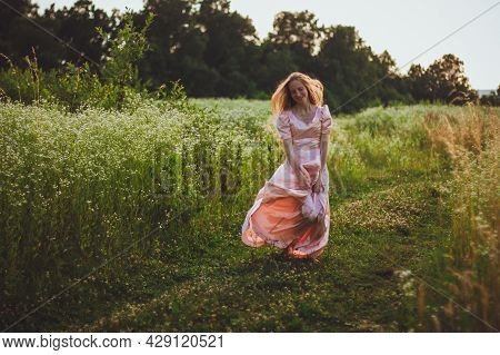Young Woman With Long Blond Hair Standing In The Wildflowers Field And Holding Her Elegant Pink Dres