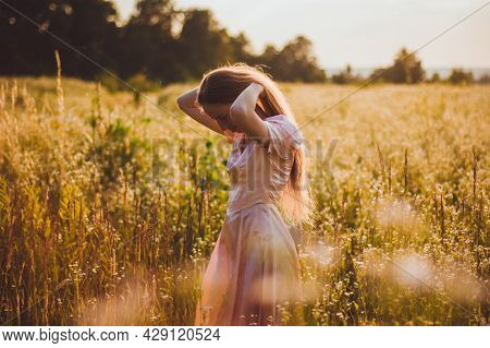 Young Woman Holding Her Long Blond Hair Standing In The Wildflowers Field In The Elegant Pink Dress