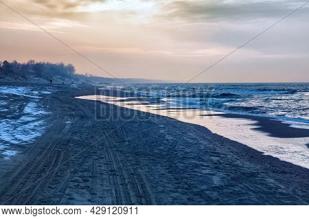 View Of The Sand Beach With The Tire Marks And Footprints On The Baltic Sea Coast At The Winter Time