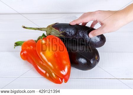 Purple Eggplants And Bulgarian Peppers In A Human Hand On White Wooden Background.