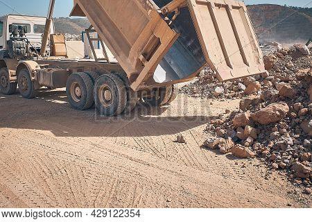 Unloading Tipper. Earthmoving Works At Construction Site. Dump Truck Unloads Soil From Truck Back