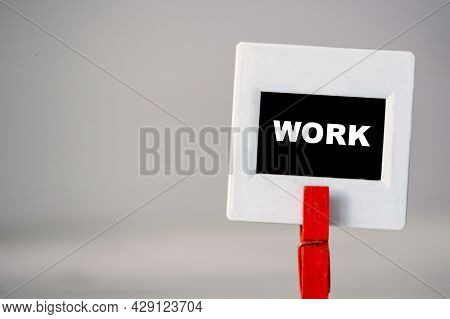 Plastic Frame With Clothes Pin On Table. White Frame With Black Background And Inscription Word Work