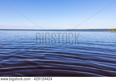 Blue Water Undulating Surface Under A Clear Sky