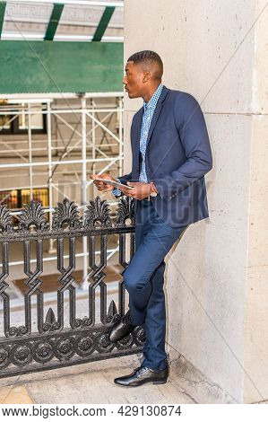 Dressing In A Blue Suit And Leather Shoes, Holding A Tablet Computer, A Young Black Businessman Is S