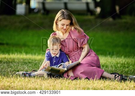 Mother And Child Lie On Grass And Read Book Outdoors.
