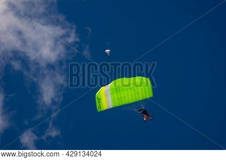 Tandem Parachute Jump, Beginner With An Instructor Hover Under A Green Canopy