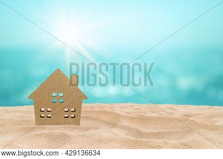 Wooden House Model On Sand Beach With Blurry Seascape View In Background.