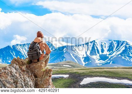 Back View A Man With A Backpack Hiker Climber Sits On The Top Of The Mountain And Looks At The Valle