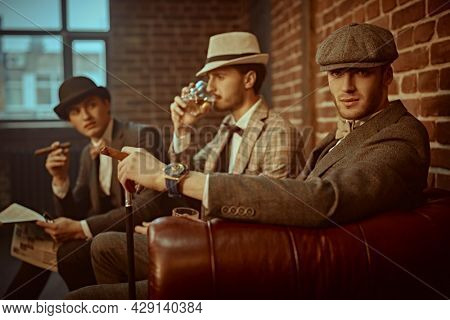 Three handsome men in elegant clothing spend time in loft interior of the club . Business people club. Men's fashion.