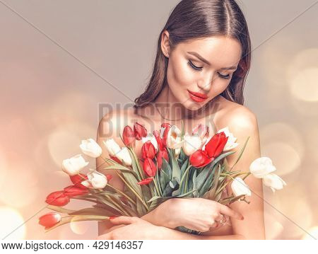 Beauty glamour girl with Spring tulips Flower bouquet. Beautiful young woman with a bunch of colorful Tulip flowers. Happy model posing with summer flowers. Valentine's Day. Birthday party. Gift