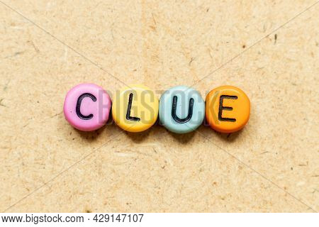 Round Color Bead With Black Letter In Word Clue On Wood Background