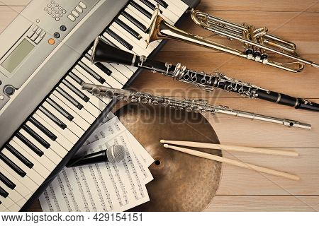 Set Of Different Musical Instruments And Microphone On Wooden Background, Flat Lay