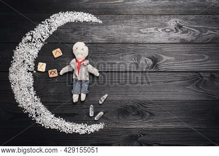 Voodoo Doll Pierced With Pins And Ceremonial Items On Black Wooden Table, Flat Lay. Space For Text