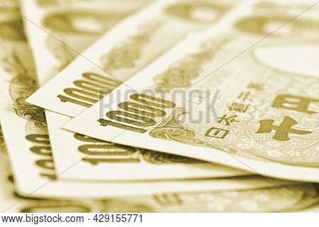 Close-up Of Several Japanese 1,000 Yen Bills. Light Green Or Olive Tinted Backdrop. Background About