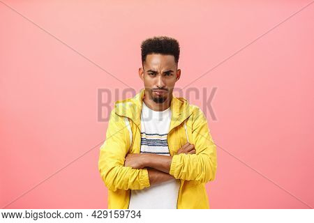 Displeased Offended Attractive African American Male With Beard And Curly Hairstyle Frowning Holding