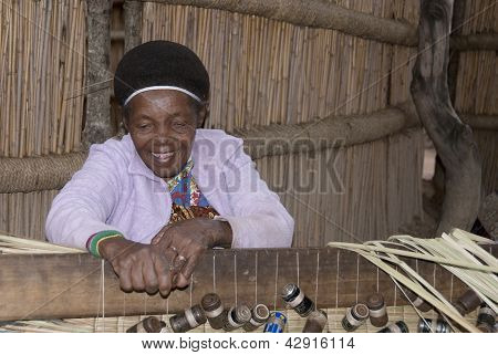 woman make carpet with straw
