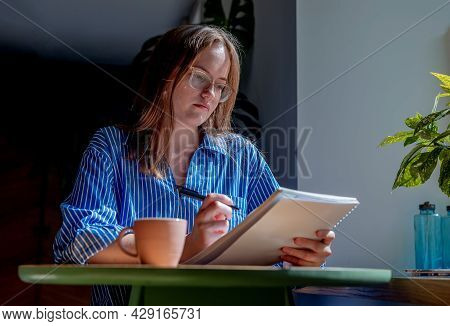 Young Woman In Eyewear Writing With Pen In Notebook, Taking Notes In Cafe With Coffee Cup On Table.