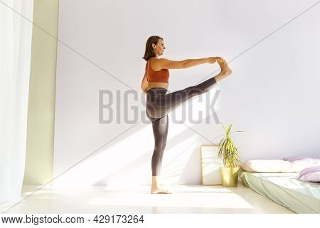 Sportive Middle-aged Attractive Brunette Woman Practicing Yoga, Doing Stretching Exercises While Sta