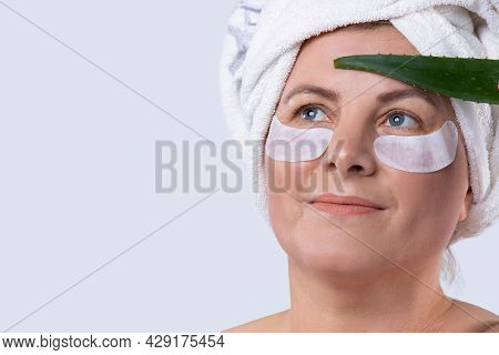 Modern Woman With Perfect Skin Applied Cosmetic Strips For Lower Eyelids And Aloe Leaf Taking Care O