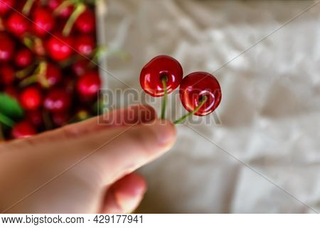 Defocus Female Hand Holding And Hanging Two Sweet Cherries Tail On Craft Wrinkled Old Paper Backgrou