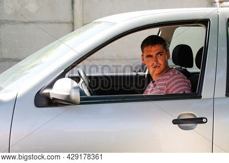 Serious Stylish Caucasian Young Man Sitting In Car. 20s Guy Driver. Silver Gray Car. Attractive Brun