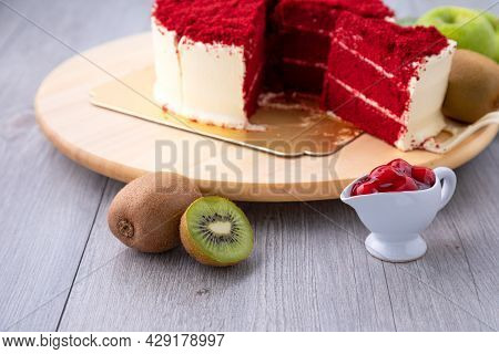 Close Up Red And Cream Cake Cutting In Piece Placing On Wooden Tray Together With Kiwi, Apple And Bl