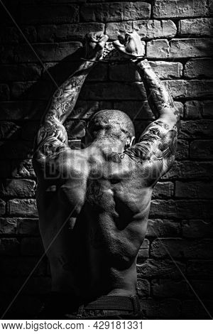 A Muscular Male Prisoner Stands With His Hands Up In Handcuffs Facing The Wall. A Dangerous Criminal