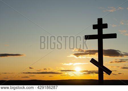 Orthodox Cross On In The Sunbeams Of The Sunset. Faith And Faith Concept. Spiritual Moment