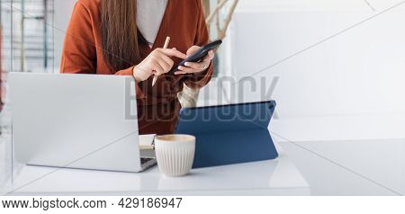 Focus on hand young asian woman using mobile phone working with laptop and tablet working or study online