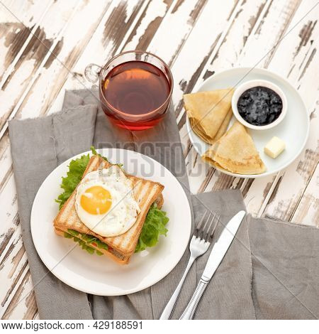 Continental American Breakfast On Wooden Rustic Background. Grilled Toast With Fried Egg, Cup Of Tea