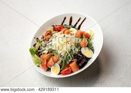 Caesar Salad With Red Fish And Grated Parmesan Cheese. Food Plate On White Background. Horizontal Fo