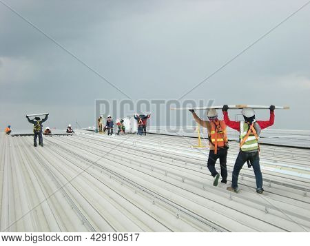 Workers Carry Solar Pv Panel On Roof Installation