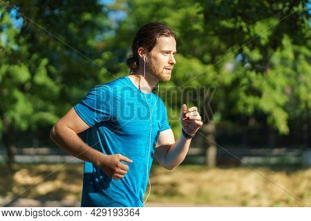 Side View Of Young Handsome Active Man In Blue Shirt Running On Hot Sunny Day In City Park, Athletic