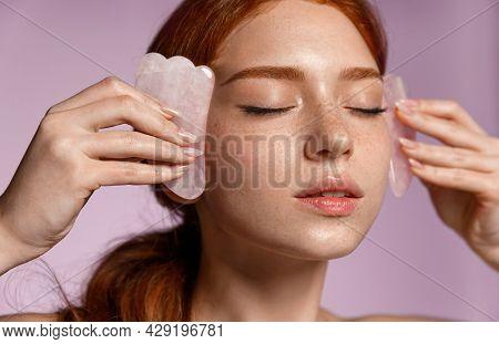 Close Up Portrait Of Beautiful Redhead Girl, Ginger Female Massaging Face With Jade Scraper, Close E