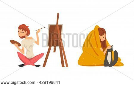Woman With Brush And Palette Painting On Drawing Easel And Covered With Blanket Stroking Cat Staying