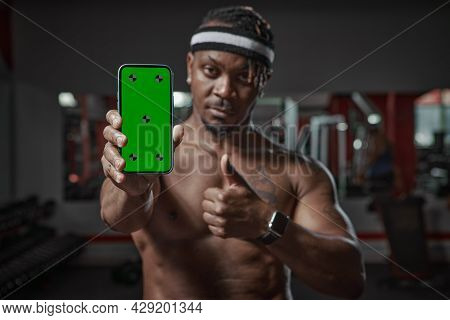 African American Man Showing Green Screen Phone With Tracking Points. Gym Workout And Sports App For