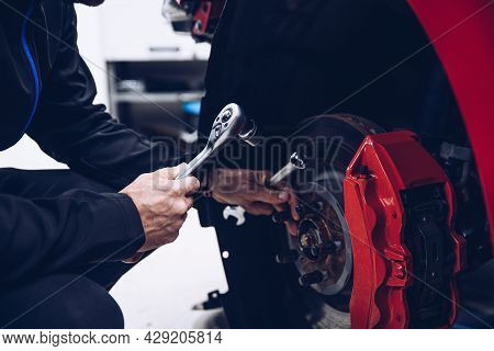 Car Mechanic Repairing Car Brakes In Car Service
