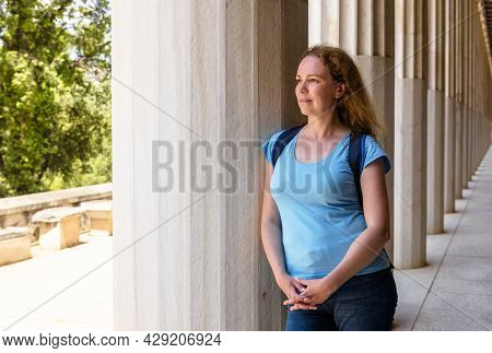 Female Tourist Visits Stoa Of Attalos, Athens, Greece, Europe. Young Pretty Woman Stands By Ancient