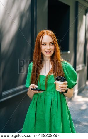Vertical Medium Shot Portrait Of Attractive Young Woman In Green Dress Holding Takeaway Coffee Cup,