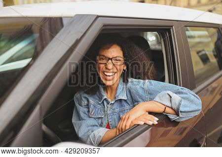 Happy Young Smiling African American Woman Black Haired Driver In Glasses Sitting In New Brown Car,