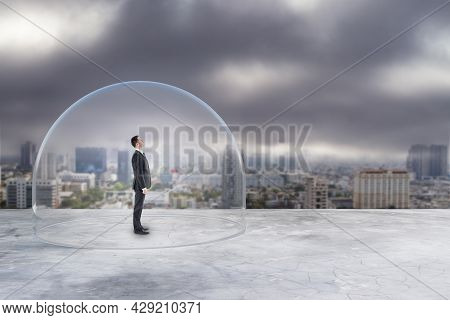 Businessman Under Glass Cover Standing On Gloomy City Background With Mock Up Place. Work Prison Con