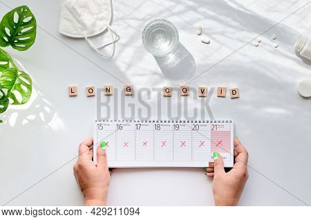 Text Long Covid, Wooden Letters. Hand With Weekly Planner, Calendar With All Days Crossed Out. Cance