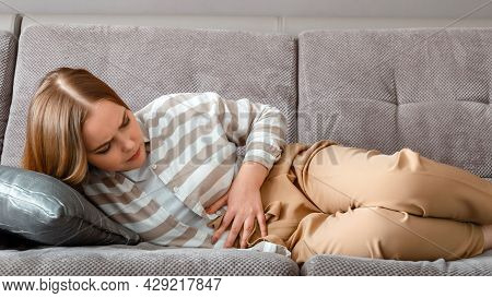 Young Woman Has Abdominal Pain Lying On Couch In Working Day In Office. Acute Pain In Bloating Pms.