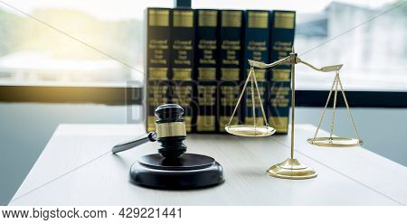 Gavel Hammer, Justice Scale, And Law Textbook On Table In Lawyer Office For Providing Legal Consult