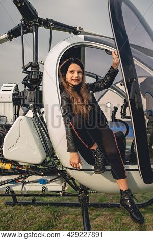 Smiling Preteen Girl Sitting In Open Cockpit Of Helicopter